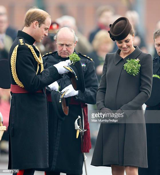 Prince William Duke of Cambridge attaches a shamrock to his cap as he and Catherine Duchess of Cambridge attend the annual St Patrick's Day Parade at...
