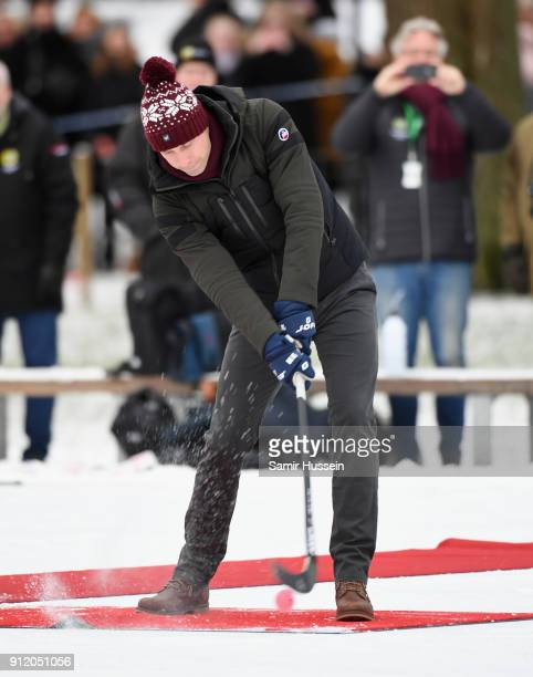 Prince William Duke of Cambridge attempts to hit the ball as he attends a Bandy hockey match with Catherine Duchess of Cambridge where they will...