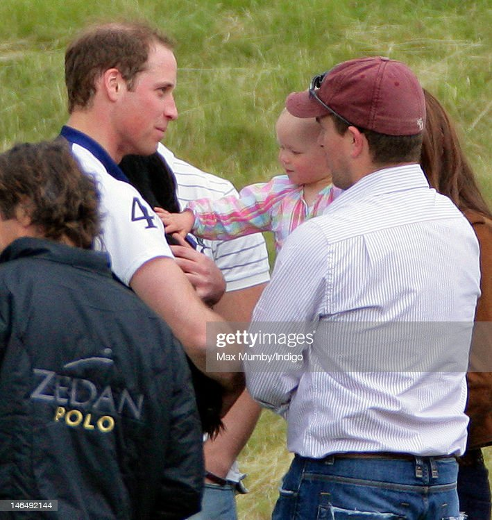 Prince William, Duke of Cambridge carries his dog Lupo as he talks with Savannah Phillips and Peter Phillips at The Golden Metropolitan Polo Club Charity Cup polo match, in which Prince William, Duke of Cambridge and Prince Harry played, at the Beaufort Polo Club on June 17, 2012 in Tetbury, England.