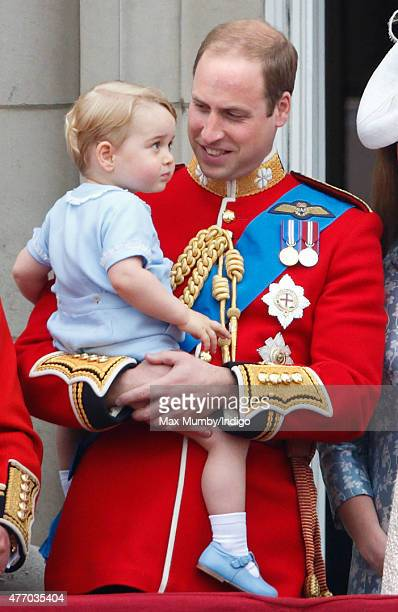 Prince William Duke of Cambridge carries his son Prince George of Cambridge as he stands on the balcony of Buckingham Palace during Trooping the...