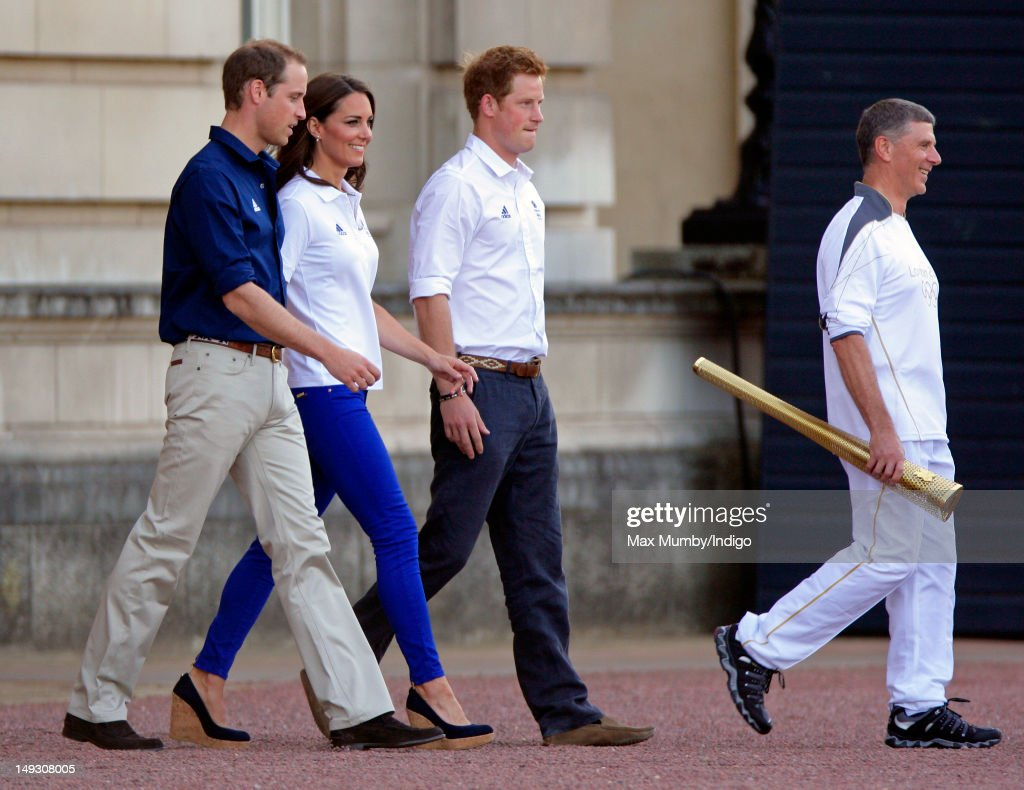 Prince William, Duke of Cambridge, Catherine, Duchess of Cambridge, Prince Harry and torch bearer John Hulse walk into the forecourt of Buckingham Palace to await the arrival of the Olympic Flame on Day 69 of the London 2012 Olympic Torch Relay on July 26, 2012 in London, England.