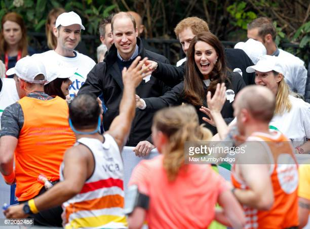 Prince William, Duke of Cambridge, Catherine, Duchess of Cambridge and Prince Harry hand out water to runners taking part in the 2017 Virgin Money...