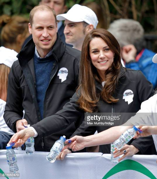 Prince William, Duke of Cambridge & Catherine, Duchess of Cambridge hand out water to runners taking part in the 2017 Virgin Money London Marathon on...