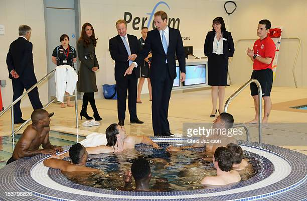 Prince William Duke of Cambridge chats to Jermaine Defoe as Catherine Duchess of Cambridge looks on in the hyrotherapy suite during the official...