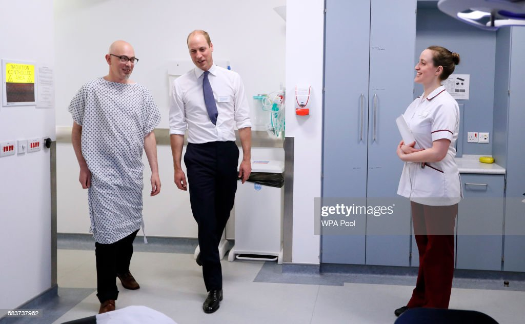 Prince William, Duke of Cambridge, escorts patient Simon, left, into a radiotherapy treatment room during a visit to the Royal Marsden hospital on May 16, 2017 in Sutton, England. The Duke of Cambridge, President of the Royal Marsden NHS Foundation Trust, visited the hospital's facilities in Sutton. During the visit, which marks 10 years since His Royal Highness became President of the centre, The Duke accompanied staff as they went about their daily activities in treating and caring for patients.