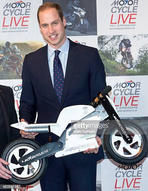 Prince William Duke of Cambridge gets given a toy motorbike for Prince George during a visit to Motorcycle Live at NEC Arena on November 30 2013 in...