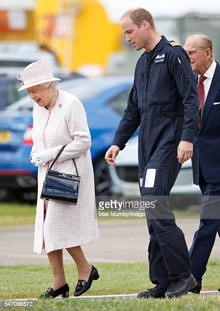 Prince William Duke of Cambridge gives his grandmother Queen Elizabeth II a tour as she opens the new East Anglian Air Ambulance base at Cambridge...