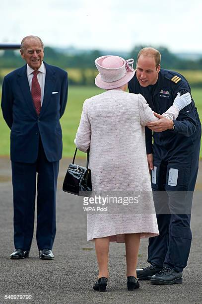 Prince William Duke of Cambridge gives Queen Elizabeth II a greeting as Prince Philip Duke of Edinburgh looks on during a tour before she opens the...