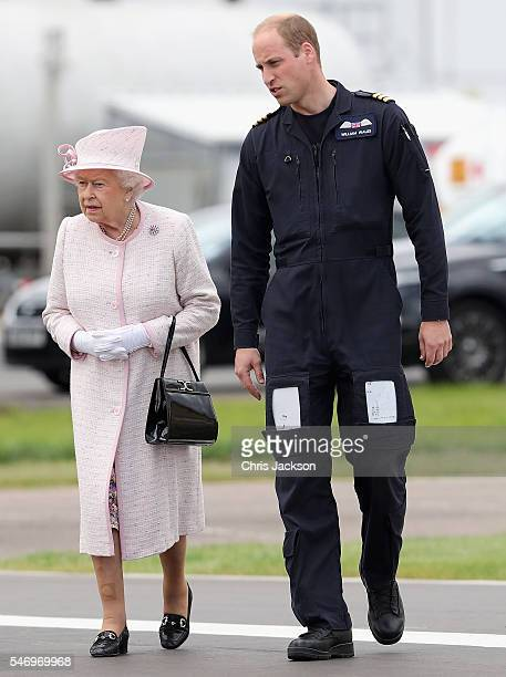 Prince William Duke of Cambridge gives Queen Elizabeth II a tour as they open the new East Anglian Air Ambulance Base at Cambridge Airport on July 13...