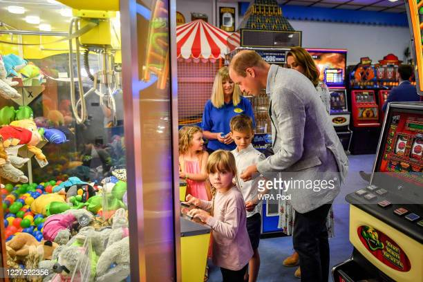 Prince William Duke of Cambridge hands a coin to Jamie Case so he and his friend Erin Phillips and sister Hollie Case can play on a grab a teddy...