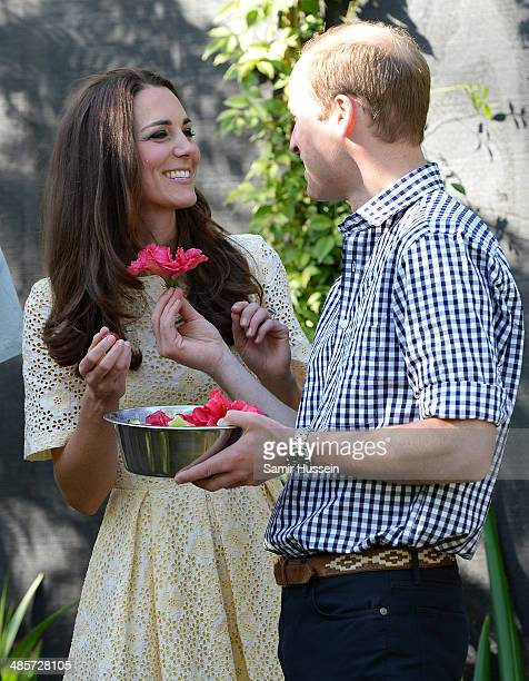 Prince William Duke of Cambridge hands Catherine Duchess of Cambridge a flower as they visit the Bilby Enclosure at Taronga Zoo on April 20 2014 in...