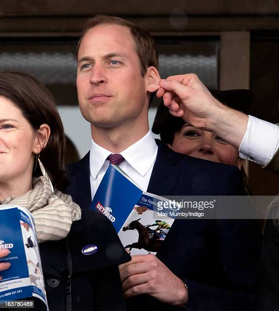 Prince William Duke of Cambridge has his ear pulled by a friend as he and Catherine Duchess of Cambridge watch the racing on Day 4 of The Cheltenham...