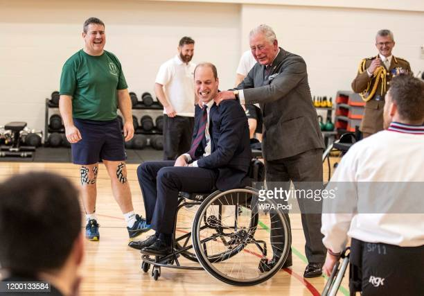 Prince William, Duke of Cambridge has his shoulders rubbed by Prince Charles, Prince of Wales after the Duke attempted and failed to throw a basket...
