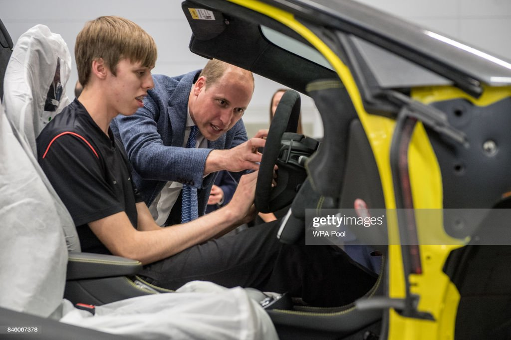 Prince William, Duke of Cambridge (R) helps fit an airbag to a McLaren car with apprentice of the year nominee Alex Machin on the factory floor during a visit to McLaren Automotive at McLaren Technology Centre on September 12, 2017 in Woking, England.