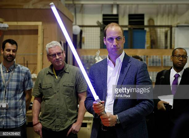 Prince William Duke of Cambridge holds a lightsaber during a tour of the Star Wars sets at Pinewood studios on April 19 2016 in Iver Heath England...