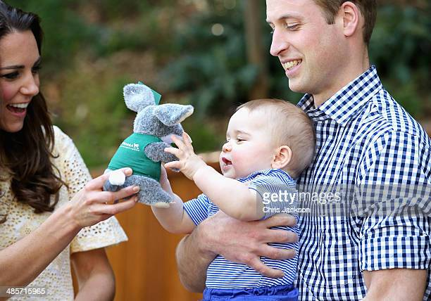 Prince William Duke of Cambridge holds Prince George of Cambridge as Catherine Duchess of Cambridge gives him a toy bilby during a visit to the Bilby...