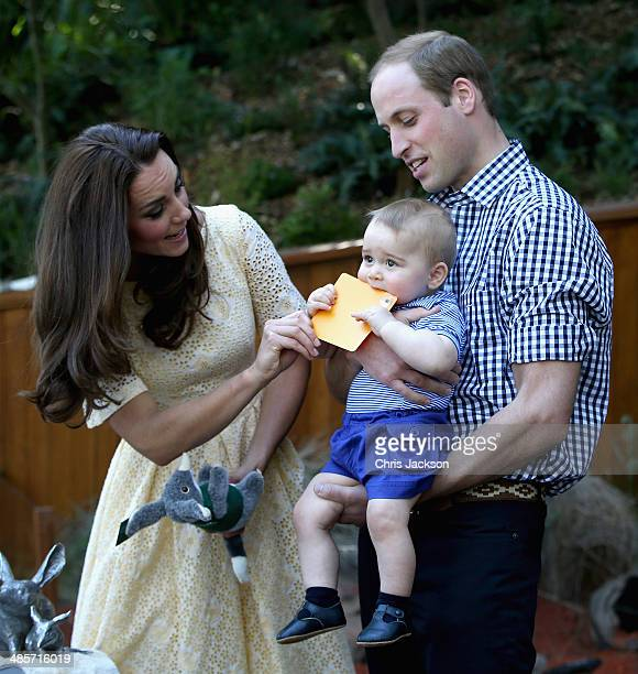 Prince William Duke of Cambridge holds Prince George of Cambridge as Catherine Duchess of Cambridge gives him a commemorative card during a visit to...