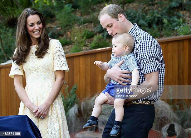 Prince William Duke of Cambridge holds Prince George of Cambridge as Catherine Duchess of Cambridge looks on during a visit to the Bilby Enclosure at...