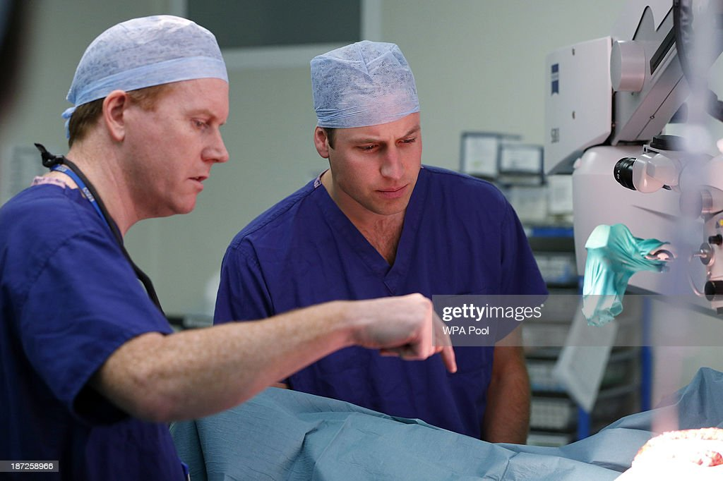 Prince William, Duke of Cambridge, in his role as President of the Royal Marsden NHS (National Health Service) Foundation Trust observes breast reconstruction surgery as lead surgeon Stuart James (L) explains part of the procedure during a visit to the Royal Marsden Hospital on November 07, 2013 in Sutton, Greater London.