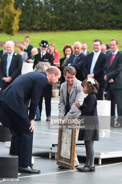 Prince William Duke Of Cambridge is greeted by a young girl of the community as he celebrates local founders during an event to mark The 50th...