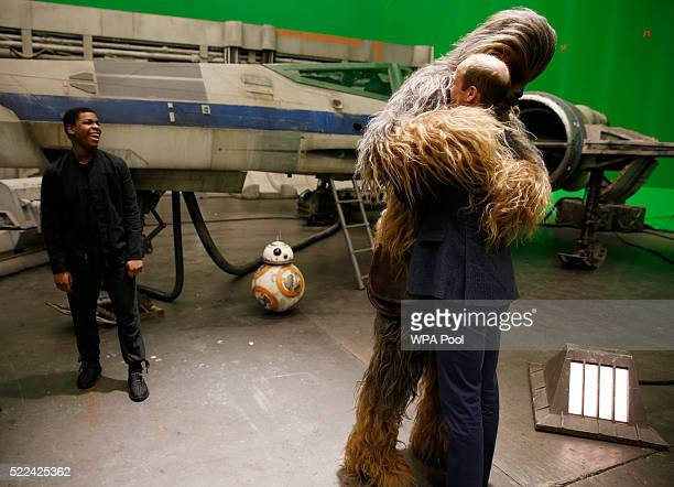 Prince William, Duke of Cambridge is hugged by Chewbacca as British actor John Boyega smiles during a tour of the Star Wars sets at Pinewood studios...
