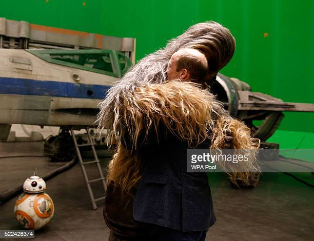Prince William Duke of Cambridge is hugged by Chewbacca during a tour of the Star Wars sets at Pinewood studios on April 19 2016 in Iver Heath...
