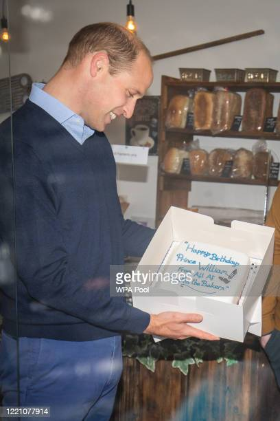 Prince William Duke of Cambridge is presented with a birthday cake by shop owner Paul Brandon during a visit to Smiths the Bakers in the High Street...