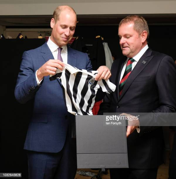Prince William Duke Of Cambridge is presented with a Newcastle United football shirt for his son Prince George as he attends a reception at the...