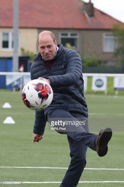 Prince William, Duke of Cambridge kicks a ball on the pitch during a visit to Spartans FC's Ainslie Park Stadium, to hear about initiatives in...
