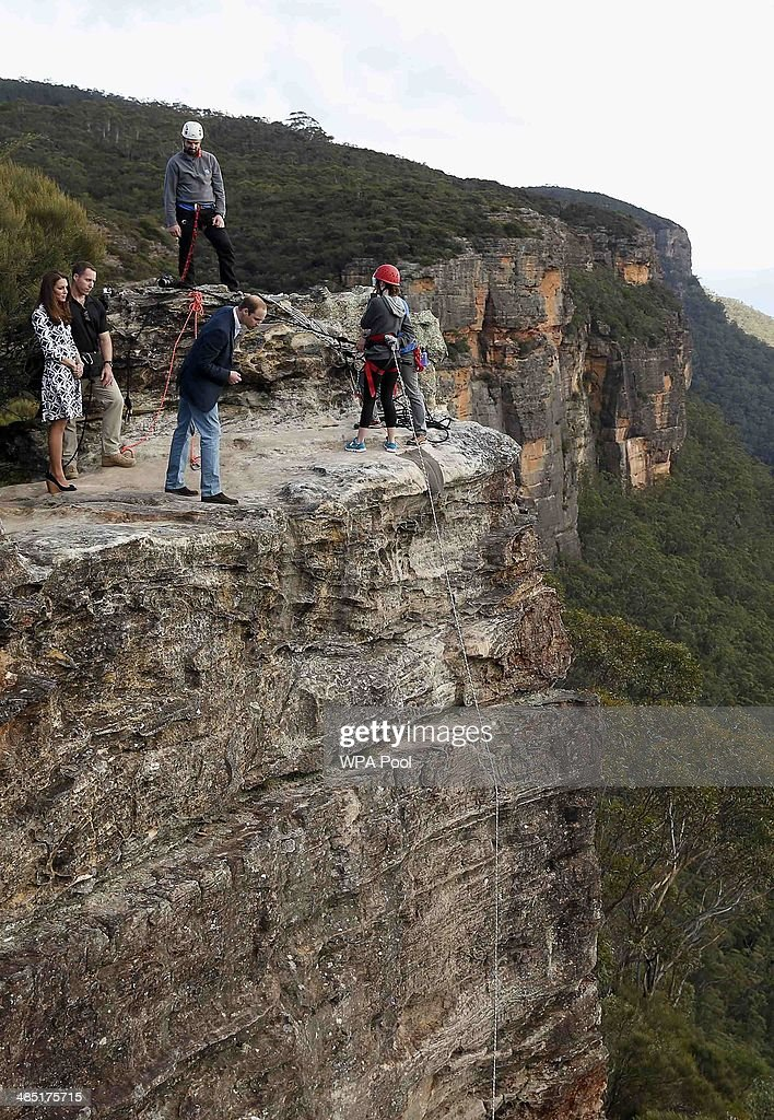 Prince William, Duke of Cambridge leans over the cliff as Catherine, Duchess of Cambridge looks on while visiting the Narrow Neck Lookout and observe abseiling by the Mountain Youth Services group in the Blue Mountains on April 17, 2014 in Katoomba, Australia. The Duke and Duchess of Cambridge are on a three-week tour of Australia and New Zealand, the first official trip overseas with their son, Prince George of Cambridge.
