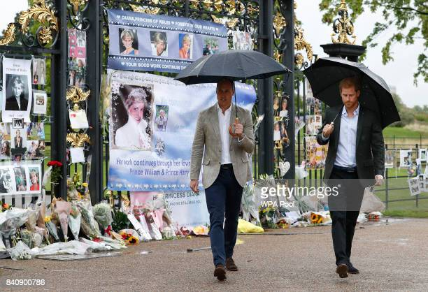 Prince William Duke of Cambridge left and Prince Harry walk away after placing flowers amongst the floral and pictorial tributes to their late mother...