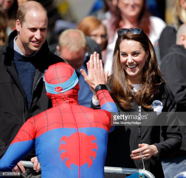 Prince William Duke of Cambridge looks on as Catherine Duchess of Cambridge high fives a runner dressed as spiderman taking part in the 2017 Virgin...