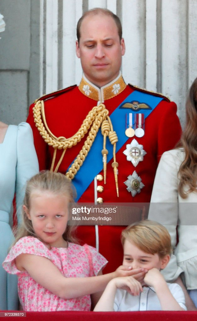 Prince William, Duke of Cambridge looks on as Savannah Phillips puts her hand over Prince George of Cambridge's mouth whilst they stand on the balcony of Buckingham Palace during Trooping The Colour 2018 on June 9, 2018 in London, England. The annual ceremony, involving over 1400 guardsmen and cavalry, is believed to have first been performed during the reign of King Charles II. The parade marks the official birthday of the Sovereign, even though the Queen's actual birthday is on April 21st.