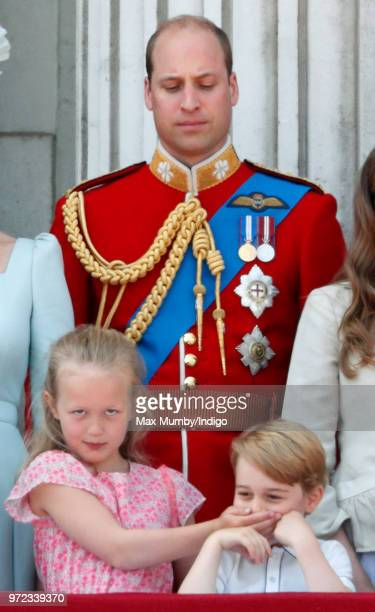 Prince William Duke of Cambridge looks on as Savannah Phillips puts her hand over Prince George of Cambridge's mouth whilst they stand on the balcony...