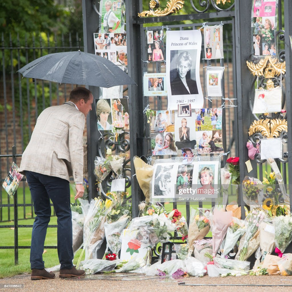 Prince William, Duke of Cambridge looks upon flowers, photos and other souvenirs left as a tribute to Princess Diana near The Sunken Garden at Kensington Palace on August 30, 2017 in London, England.