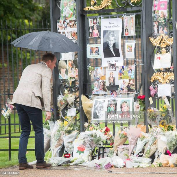 Prince William Duke of Cambridge looks upon flowers photos and other souvenirs left as a tribute to Princess Diana near The Sunken Garden at...