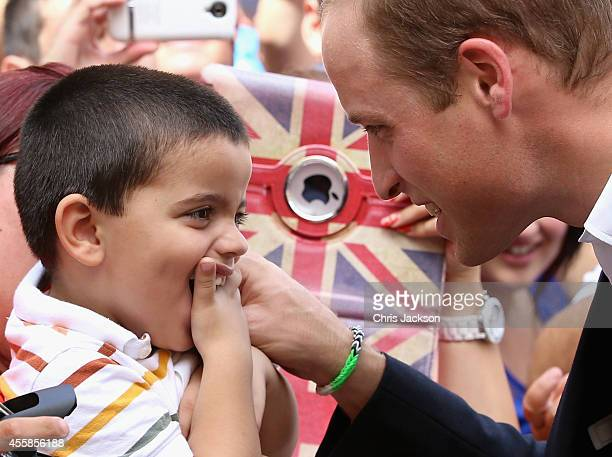 Prince William Duke of Cambridge meets a young boy during a walkabout in Vittoriosa Square on an official visit to Malta on September 21 2014 in...