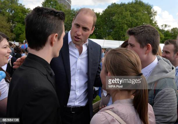 Prince William Duke of Cambridge meets guests as they host a tea party in the grounds of Buckingham Palace to honour the children of those who have...