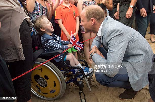 Prince William Duke of Cambridge meets Jaydon MitchellTomlinson who suffers from cerebal palsey as he visits the work of the Wave Project on...