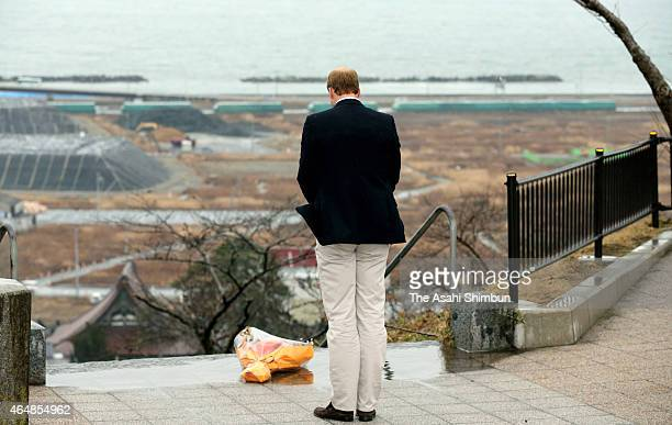 Prince William Duke of Cambridge offers a prayer toward tsunami devastated area from Hiyoriyama Park on March 1 2015 in Ishinomaki Miyagi Japan The...