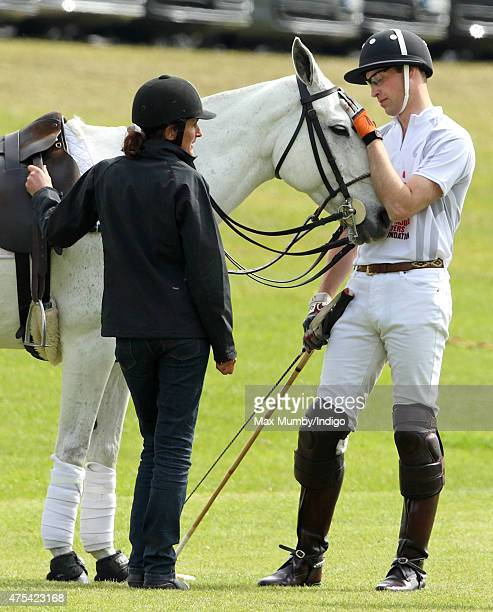 Prince William Duke of Cambridge pats his polo pony during a break in play on day 2 of the Audi Polo Challenge at Coworth Park on May 31 2015 in...