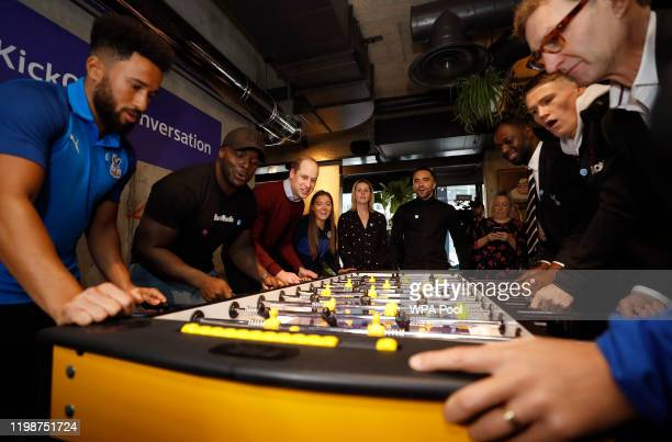 Prince William Duke of Cambridge plays table football with Crystal Palace winger Andros Townsend Wycombe Wanderers striker Adebayo Akinfenwa and...