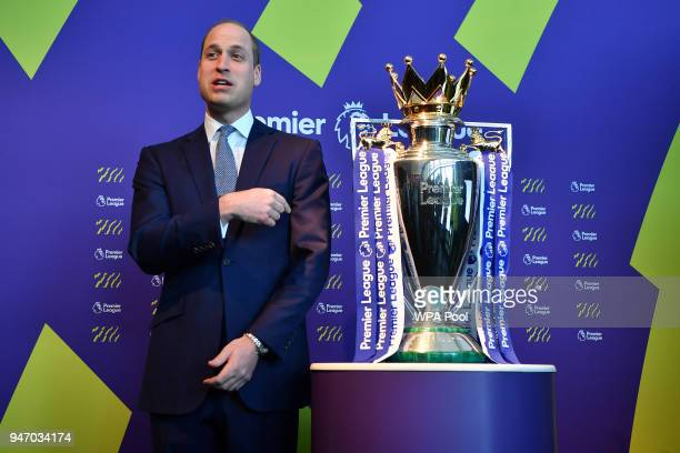 Prince William Duke of Cambridge points to the English Premier League football trophy during a 'Welcome to the UK' reception on the opening day of...