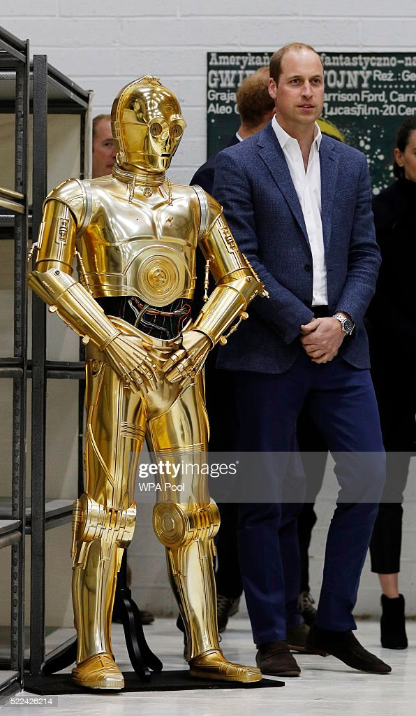 Prince William, Duke of Cambridge (R) poses next to the droid C3P0 from Star Wars as they visit the creature and droid department at Pinewood studios on April 19, 2016 in Iver Heath, England. Prince William and Prince Harry are touring Pinewood studios to visit the production workshops and meet the creative teams working behind the scenes on the Star Wars films.