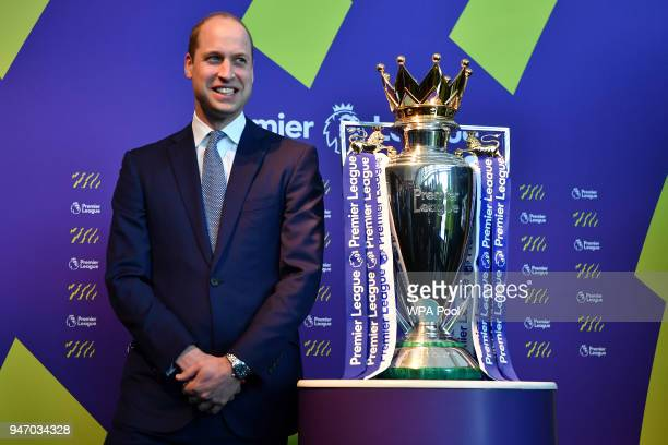 Prince William Duke of Cambridge poses next to the English Premier League football trophy during a 'Welcome to the UK' reception on the opening day...