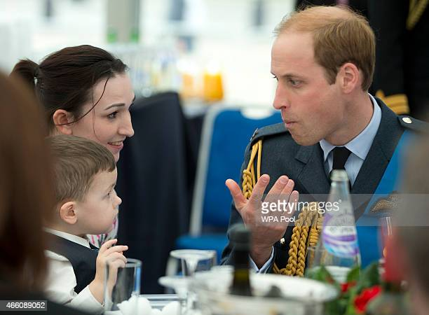 Prince William, Duke of Cambridge reacts after eating a piece of chocolate cake handed to him by Logan Prior who sits with his mother Emily at a...