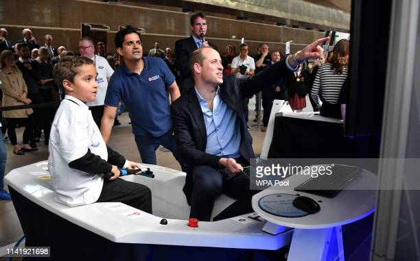 Prince William Duke of Cambridge reacts as he uses a sailing dinghy simulator during the launch the King's Cup Regatta at Cutty Sark Greenwich on May...