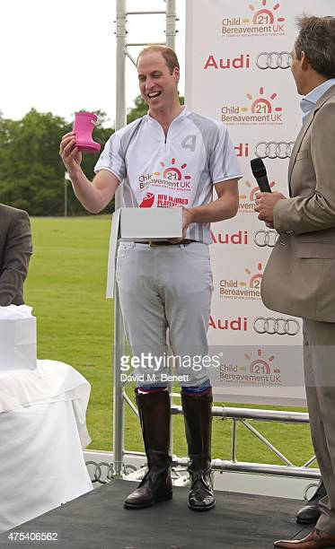 Prince William Duke of Cambridge receives a gift for his new daughter Princess Charlotte of Cambridge from Andre Konsbruck Director of Audi UK during...