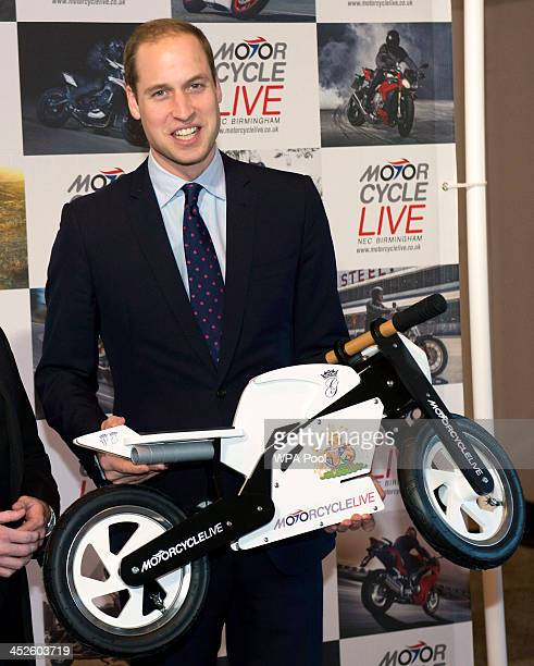 Prince William Duke of Cambridge receives a mini motorcycle as a gift for his son Prince George during a visit to Motorcycle Live at the National...
