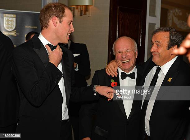 Prince William Duke of Cambridge shares a joke with FA Chairman Greg Dyke and UEFA President Michel Platini as he attends The Football Association's...